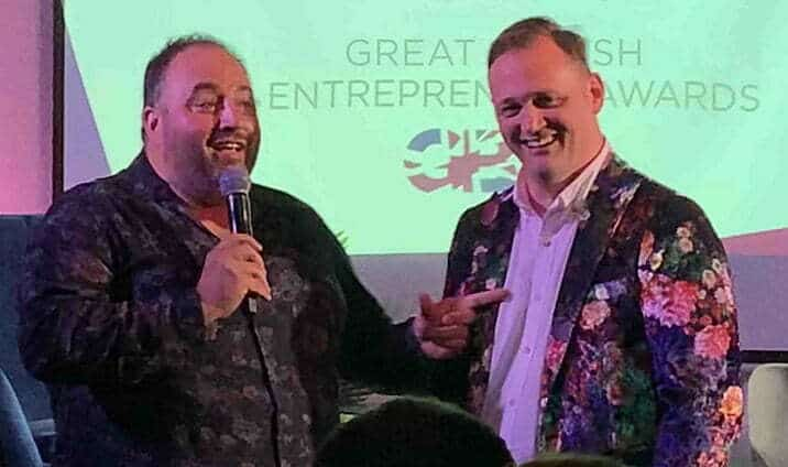 Welsh opera singer Wynne Evans and popcorn founder Simon Washbrook, in a floral jacket, speaking at a Great British Entrepreneur Awards event